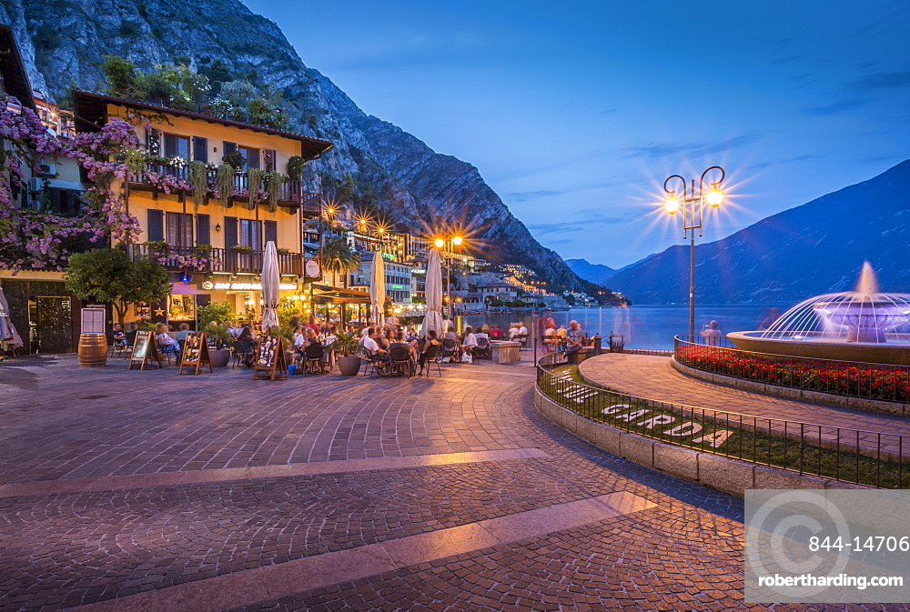 View of illuminated promenade at the port of Limone at dusk, Lake Garda, Lombardy, Italian Lakes, Italy, Europe