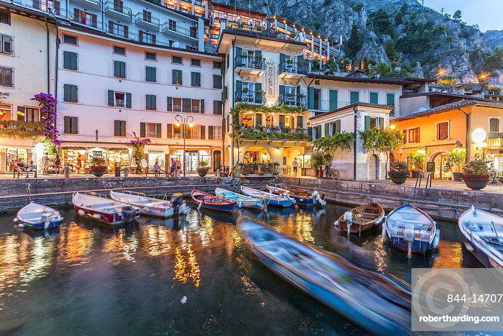View of Illuminated promenade at the port of Limone at dusk, Lake Garda, Lombardy, Italy, Europe