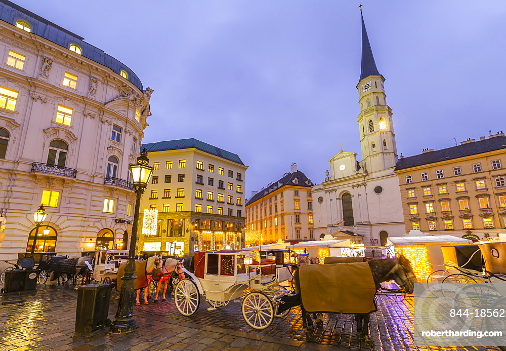 Christmas Market stalls and St. Michael Catholic Church in Michaelerplatz, Vienna, Austria, Europe