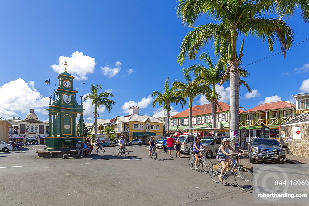 View of cyclists in The Circus and Memorial Clock, Basseterre, St Kitts & Nevis, West Indies, Caribben, Central America