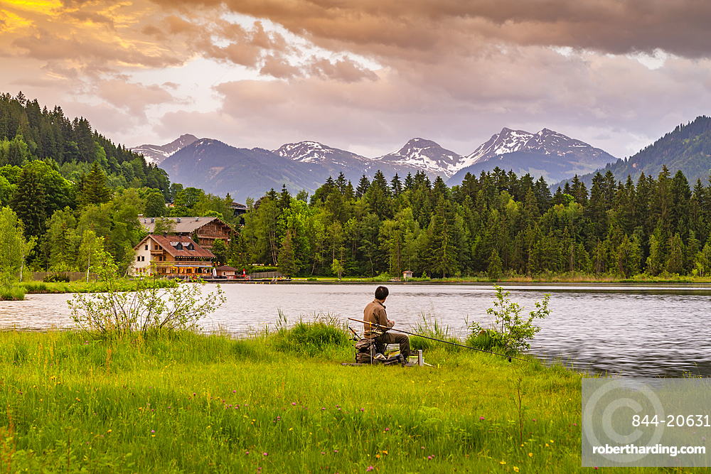 Fisherman and mountainous backdrop at Schwarzsee near Kitzbuhel, Austria, Europe