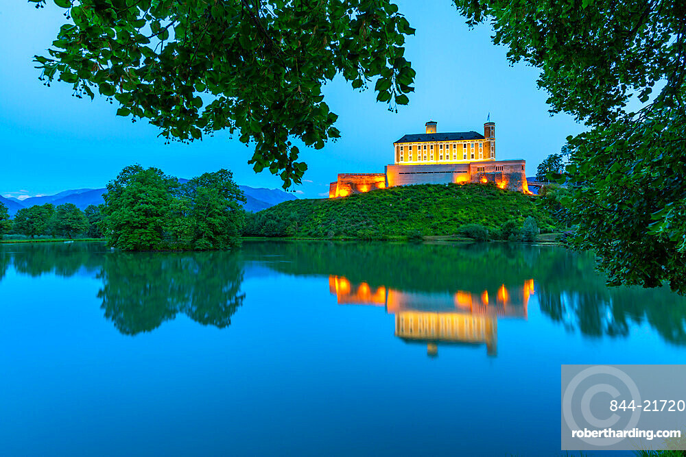 View of Trautenfels Castle reflected in nearby lake at dusk, Styria, Austria. Europe