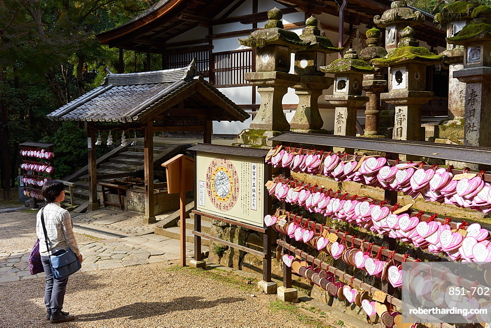 Stone lanterns and heart-shaped votives wishing good luck to new marriages at Kasuga Wakamiya Shrine in Nara, Honshu, Japan, Asia