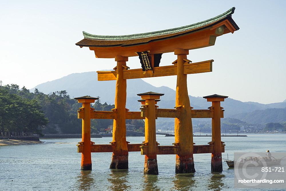 Tourist passing through the floating red wooden torii gate of Miyajima, Itsukushima, UNESCO World Heritage Site, Hiroshima Prefecture, Honshu, Japan, Asia