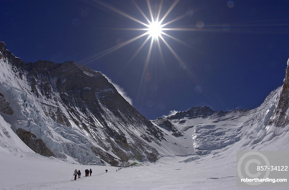 Climbers make their way to Advanced Basecamp (ABC) through the massive Western Cwm (glacial valley) on the Southeast Ridge route on Mt. Everest, Nepal. Everest's Southwest Face rises to the left with Lhotse and the Lhotse Face in the distance. Jake Norton, 4, 20, 2002, Western Cwm, Everest, Nepal.
