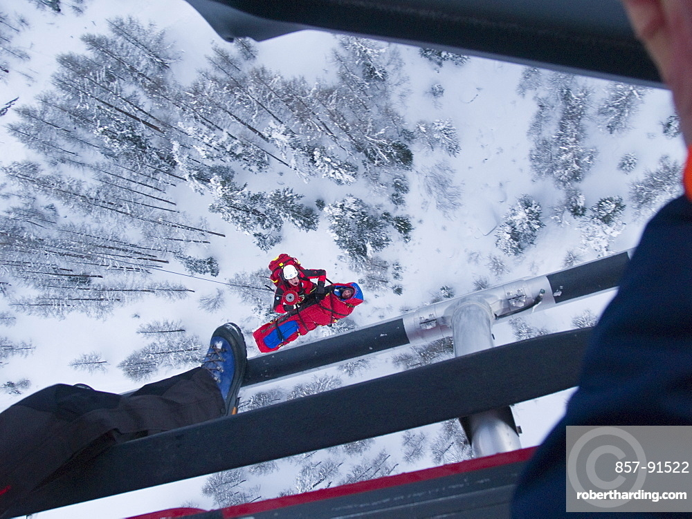 An emergency doctor is together with a patient being hosted up to a rescue helicopter in the Swiss Alps.