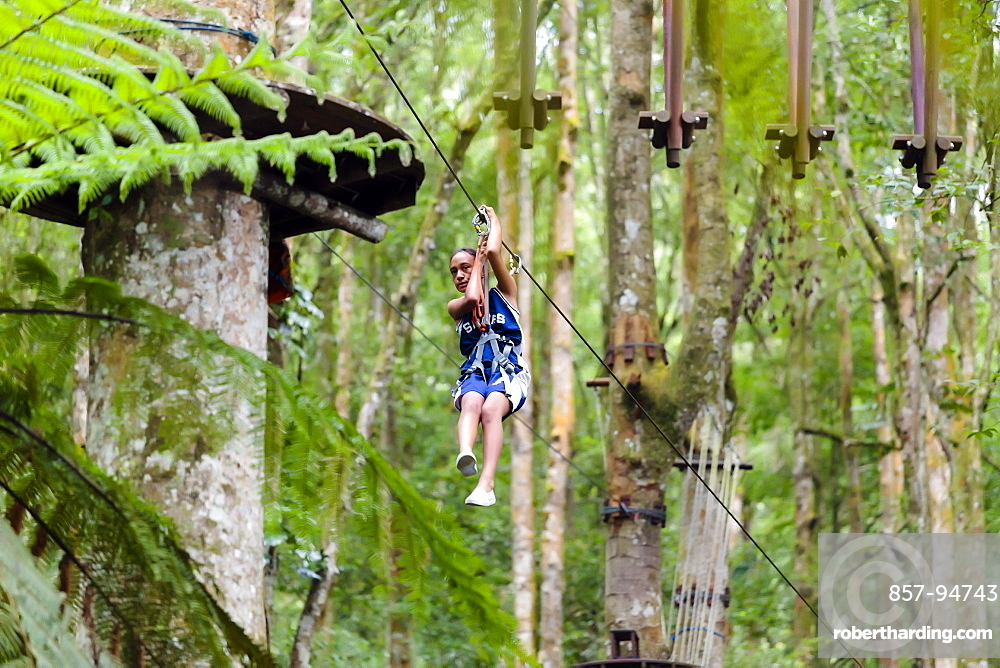 A girl descends a zipline at a Treetop Adventure Park, Bali, Indonesia
