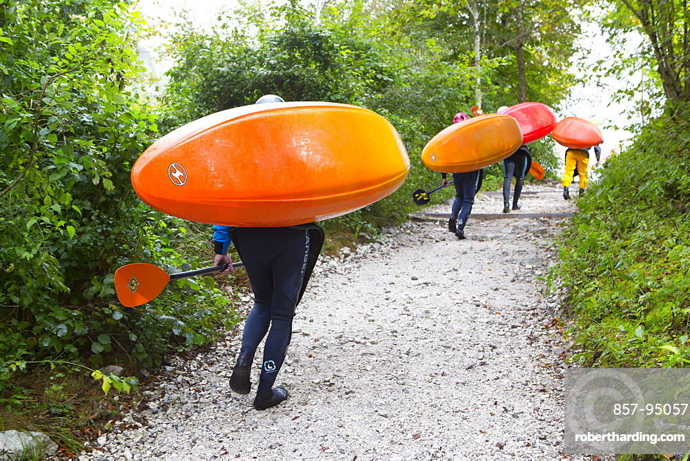 Kayakers carrying their colorful kayaks to river Soca near Bovec, Triglav, Slovenia