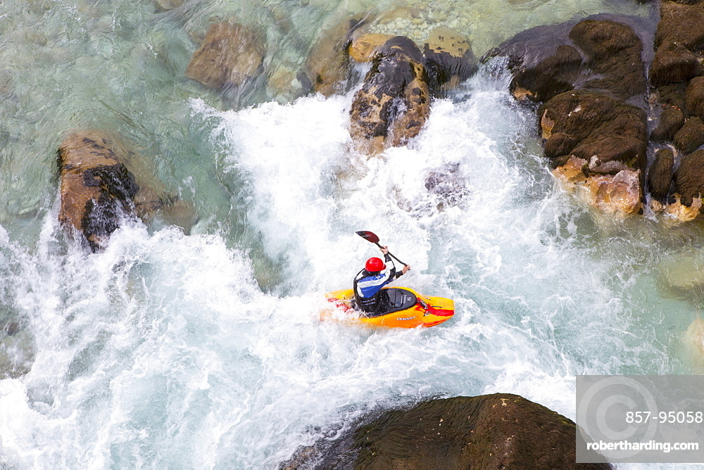 Male kayaker crossing whirlpool in green colored Soca river near Bovec, Slovenia