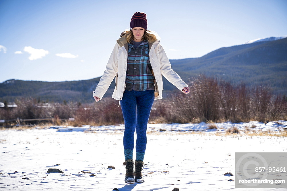 Front view full length shot of single woman walking outdoors in winter