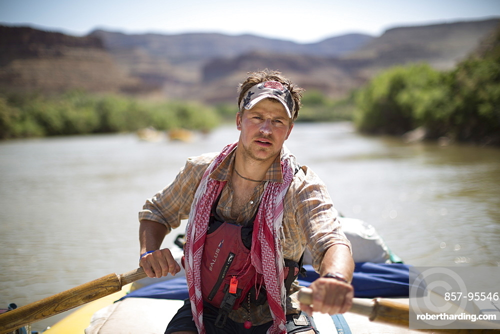 Raft guide man rowing and looking at camera during rafting trip, Desolation/Gray Canyon section, Utah, USA
