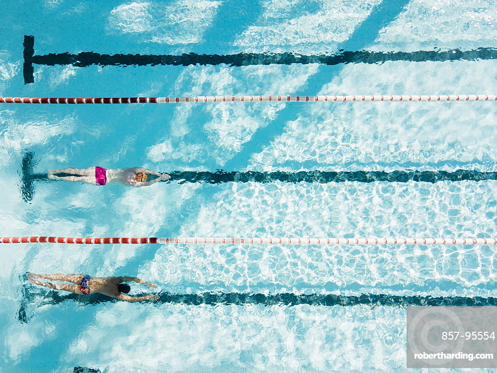 Aerial view of two swimmers in swimming pool, Mallorca, Balearic Islands, Spain