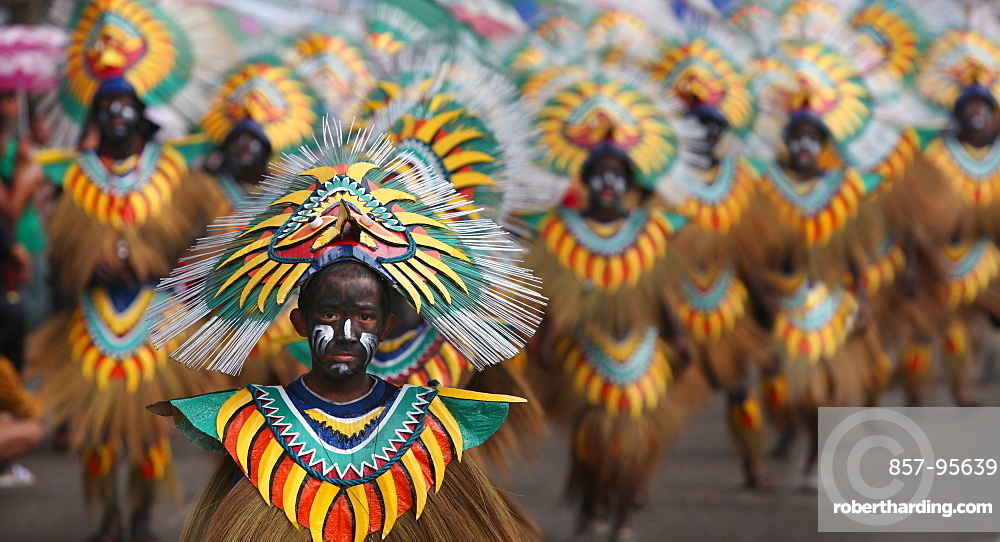 Boy with painted face in tribal costume in front of large group of people in tribal costumes during Ati Atihan Festival, Kalibo, Aklan, Panay Island, Philippines
