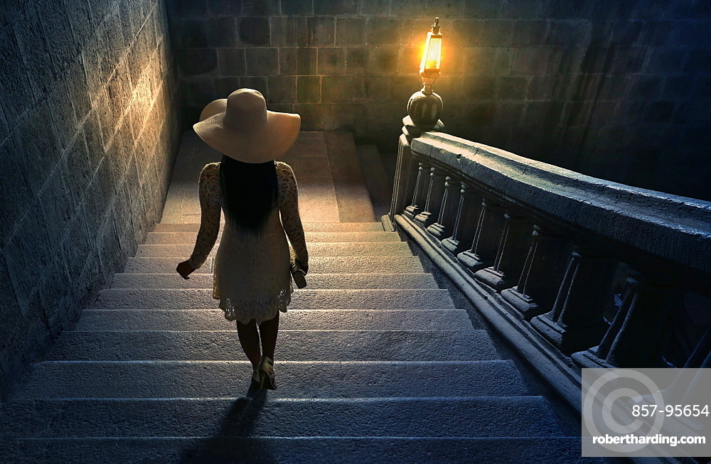 Woman in white lace dress and hat walking down stairs on colonial staircase in San Agustin Church, Manila, Philippines