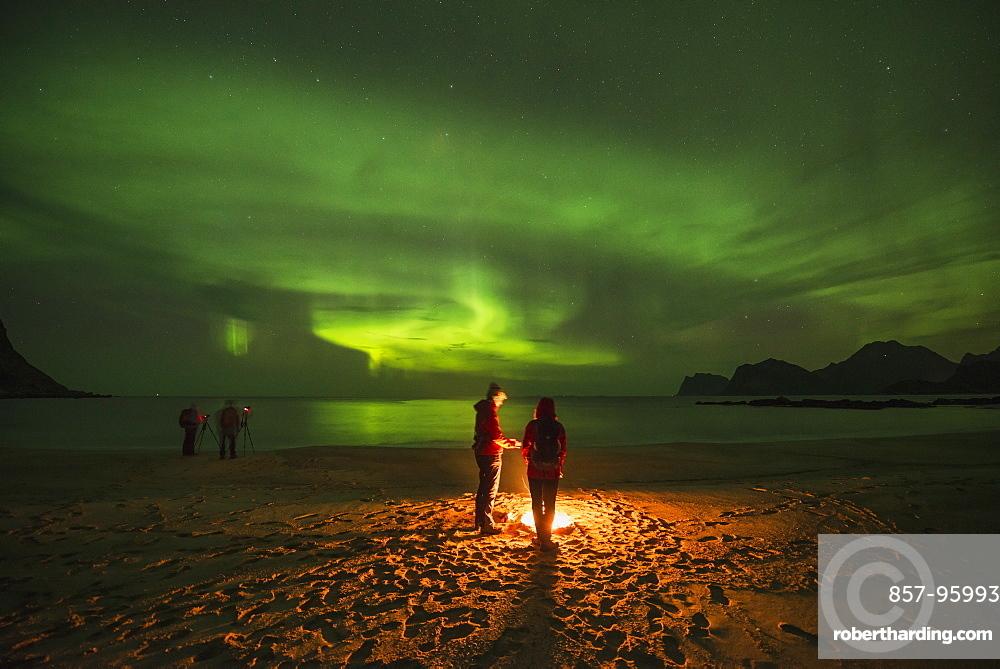 Tranquil scene with people around campfire on beach under aurora?borealis?at night, Flakstadoya, Lofoten Islands, Norway