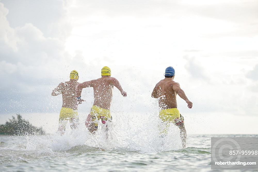 Rear view of three men in swimming caps and swimming trunks running into sea at Playa del Carmen, Quintana Roo, Mexico
