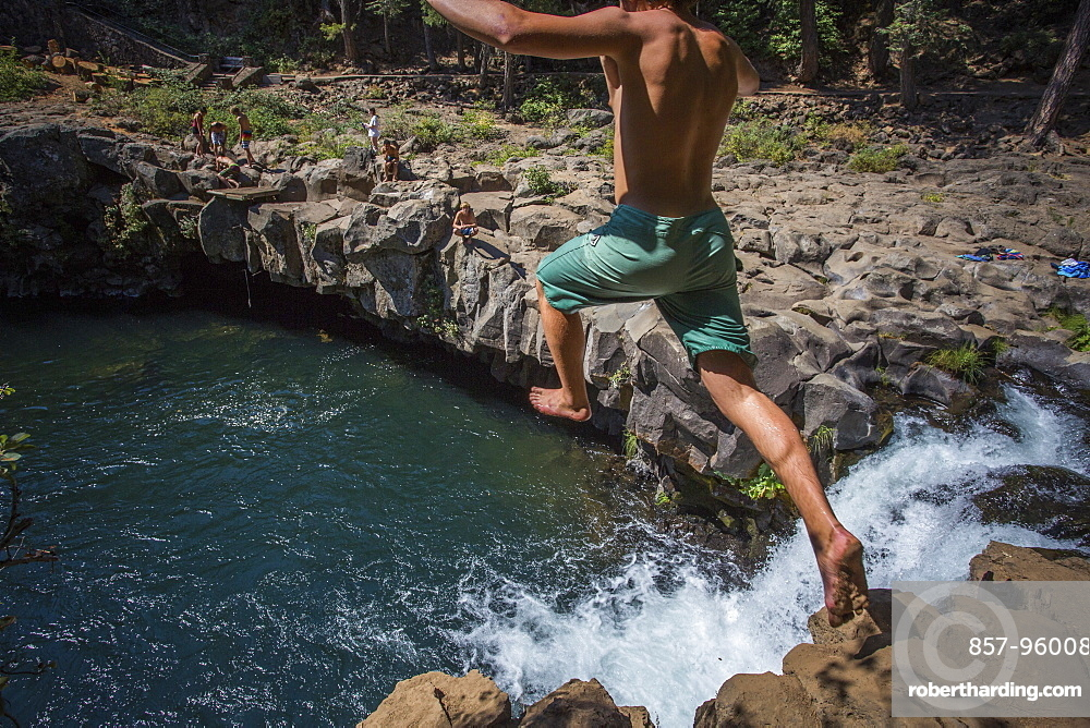 Rear view of single shirtless young man cliff jumping into?McCloud?River, California, USA