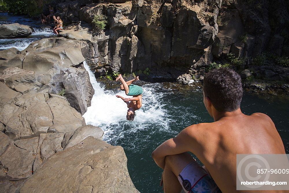 Young man cliff jumping near waterfall and another watching, ?McCloud?River, California, USA