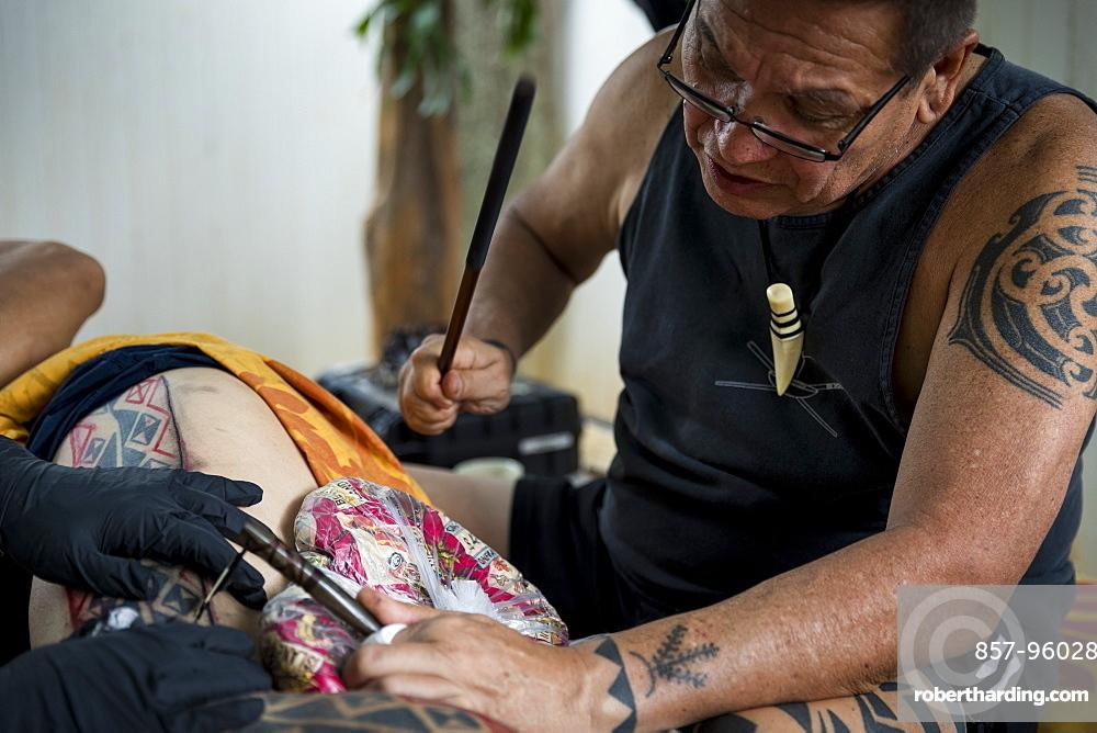 Side view of Hawaiian tattoo artist making tattoo, Oahu, Hawaii Islands, USA