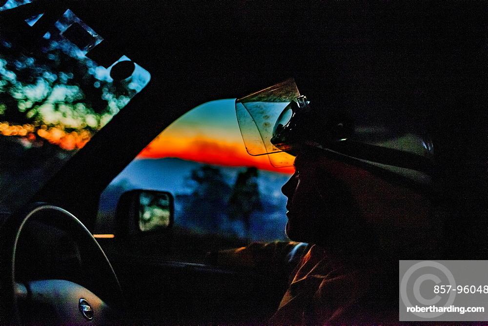 An Australian volunteer firefighter patrolling at first light, Guanaba, Queensland, Australia