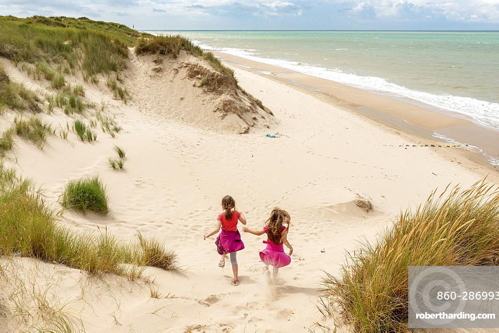 Little girls running in the dunes of the Opal Coast, summer, Pas de Calais, France