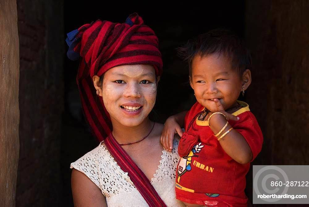 Burmese girl of Pao ethnic group carrying her little sister in the city of Nyuang U