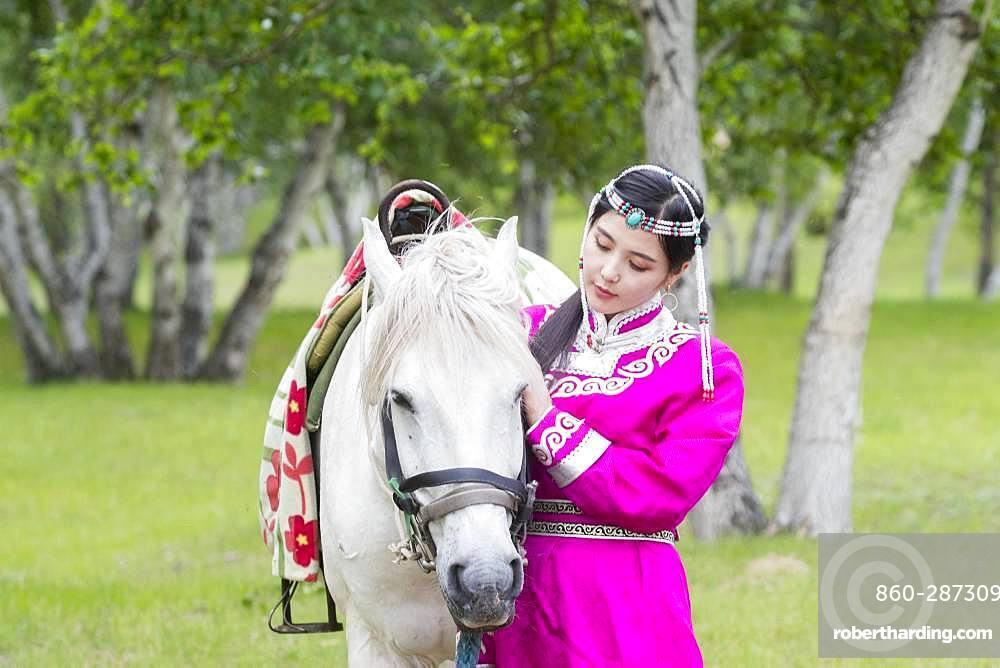 Mongol woman traditionnaly dressed with a horse, Mode, Bashang Grassland, Zhangjiakou, Hebei Province, Inner Mongolia, China