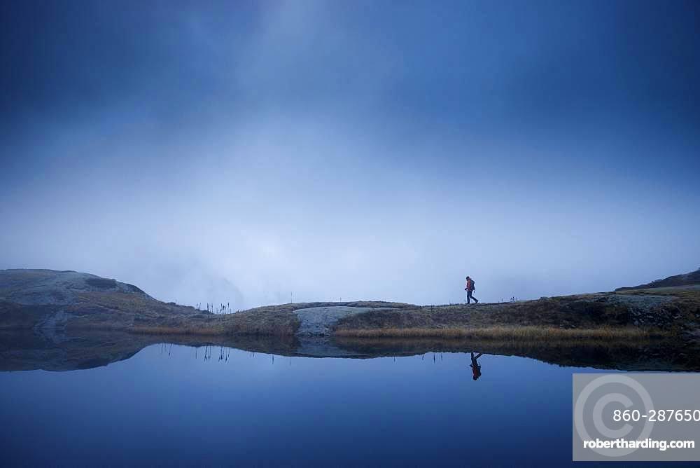 Hiker at Lake Lauzon (2008m), La Chapelle-en-Valgaudemar, Ecrins National Park, Hautes-Alpes, France
