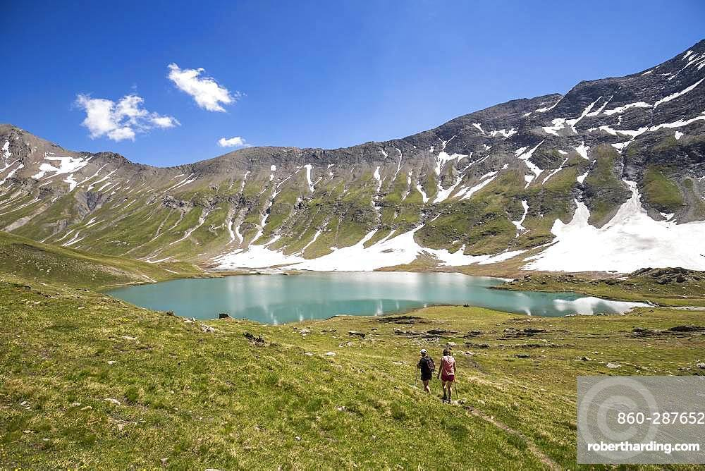 A couple of hikers walk to Lake Goleon (2438m) in the Oisans massif, ecrins National Park, Hautes-Alpes, France