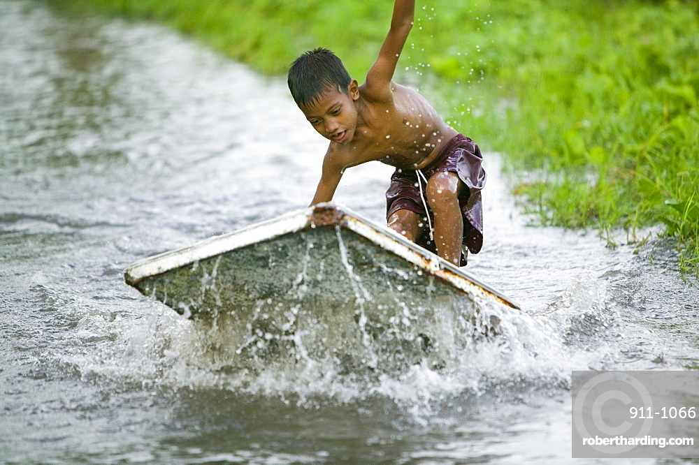 Boy playing in the floodwater caused by sea water incursion due to global warming induced sea level rise that threatens the future of these low lying islands, Funafuti Atoll, Tuvalu, Pacific