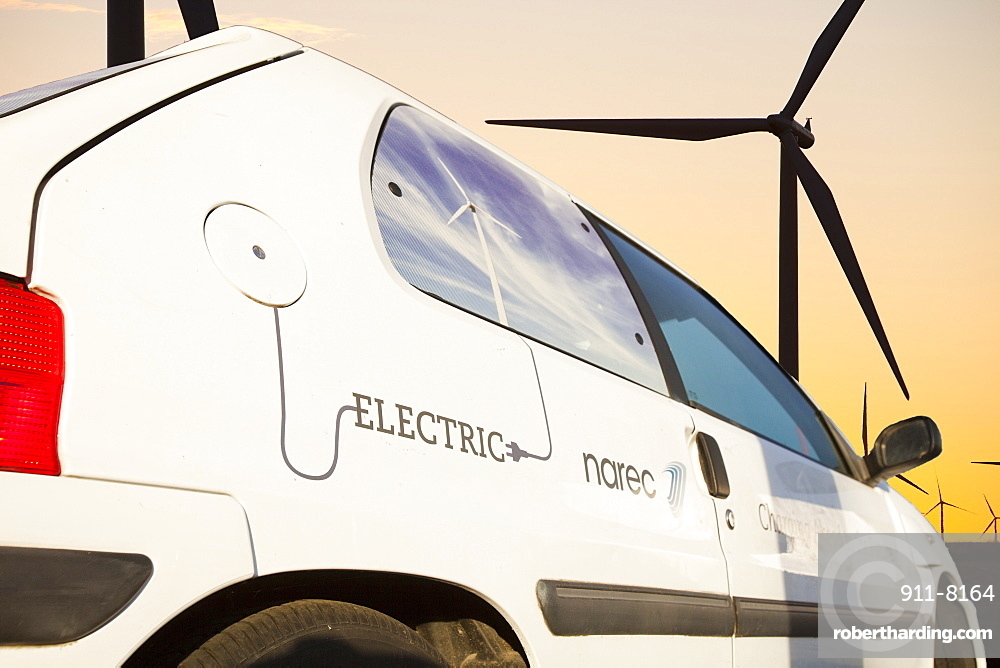 An electric car at dawn over Whitlee wind farm on Eaglesham Moor just south of Glasgow in Scotland, United Kingdom, Europe