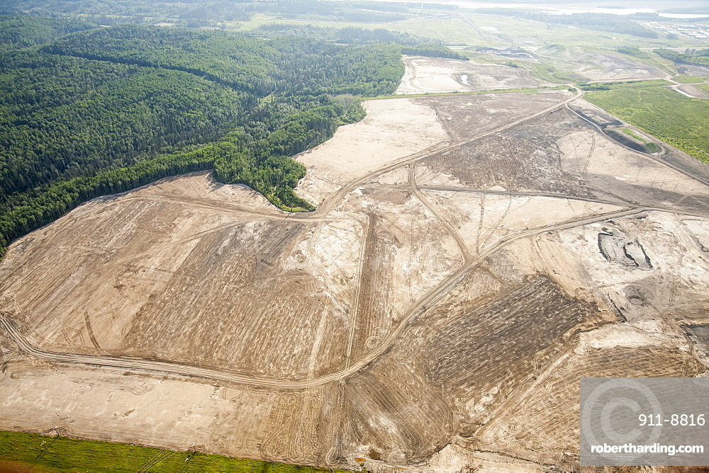 Soil overburden being removed to reach the tar sands beds in an open pit tar sands mine north of Fort McMurray, Alberta, Canada, North America