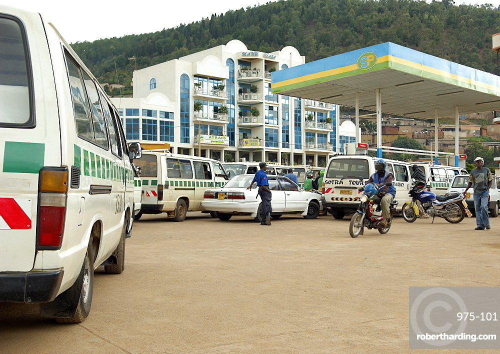 Running out of Petrol is commonplace in Rwanda.  Here, a petrol station in Kigali is filling up with vehicles but are having little joy with sourcing any petrol.  The ubiquitous armed security guard casually stands watching the chaos. Kigali, Rwanda, East Africa