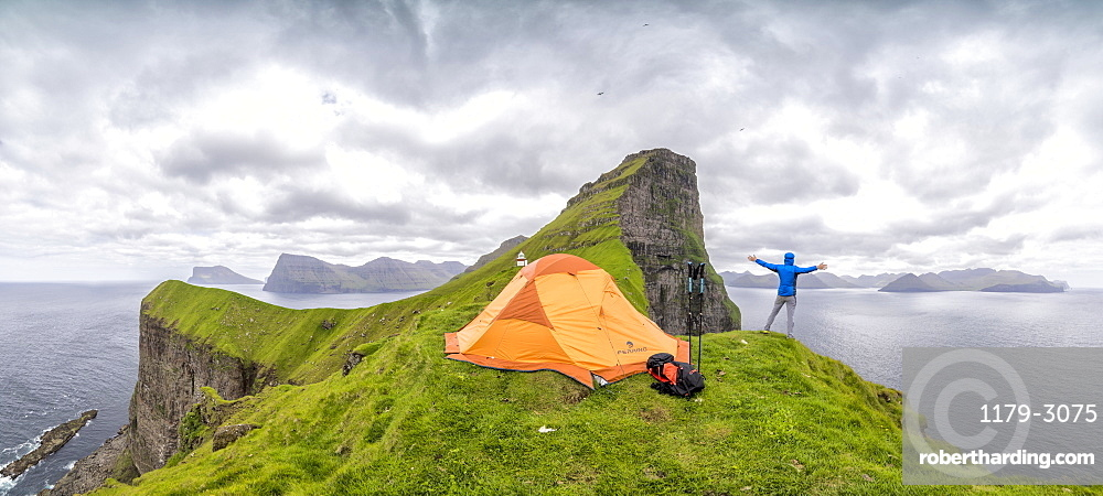 Panoramic of hiker and tent around Kallur Lighthouse, Kalsoy Island, Faroe Islands, Denmark, Europe