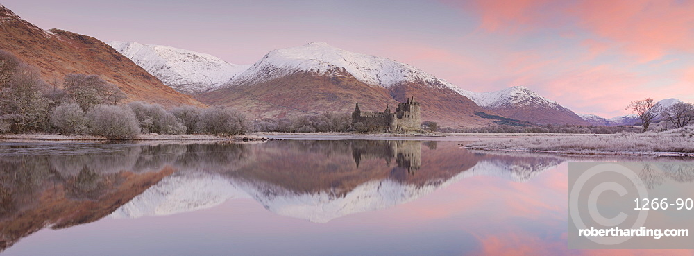 Stitched panoramic image of Kilchurn Castle and Loch Awe at sunrise with snow capped mountains in winter Argyll & Bute Scotland