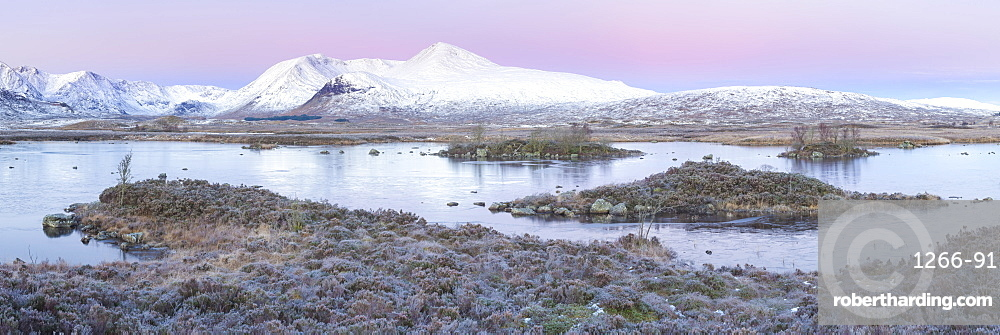 Pink sunrise and snow covered Black Mount from a frozen Lochan-na h'achlaise, Rannoch Moor, Glencoe, Highlands, Scotland