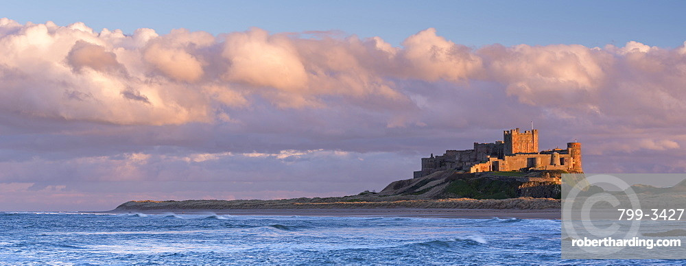 Late evening sunlight bathes the Bamburgh Castle stronghold on the Northumberland coast, Northumberland, England, United Kingdom, Europe