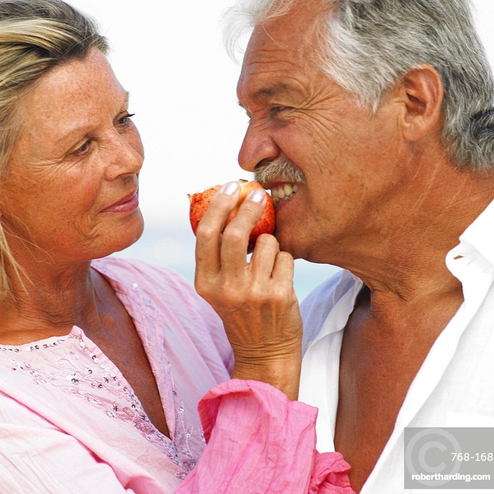 senior couple on beach holding apple