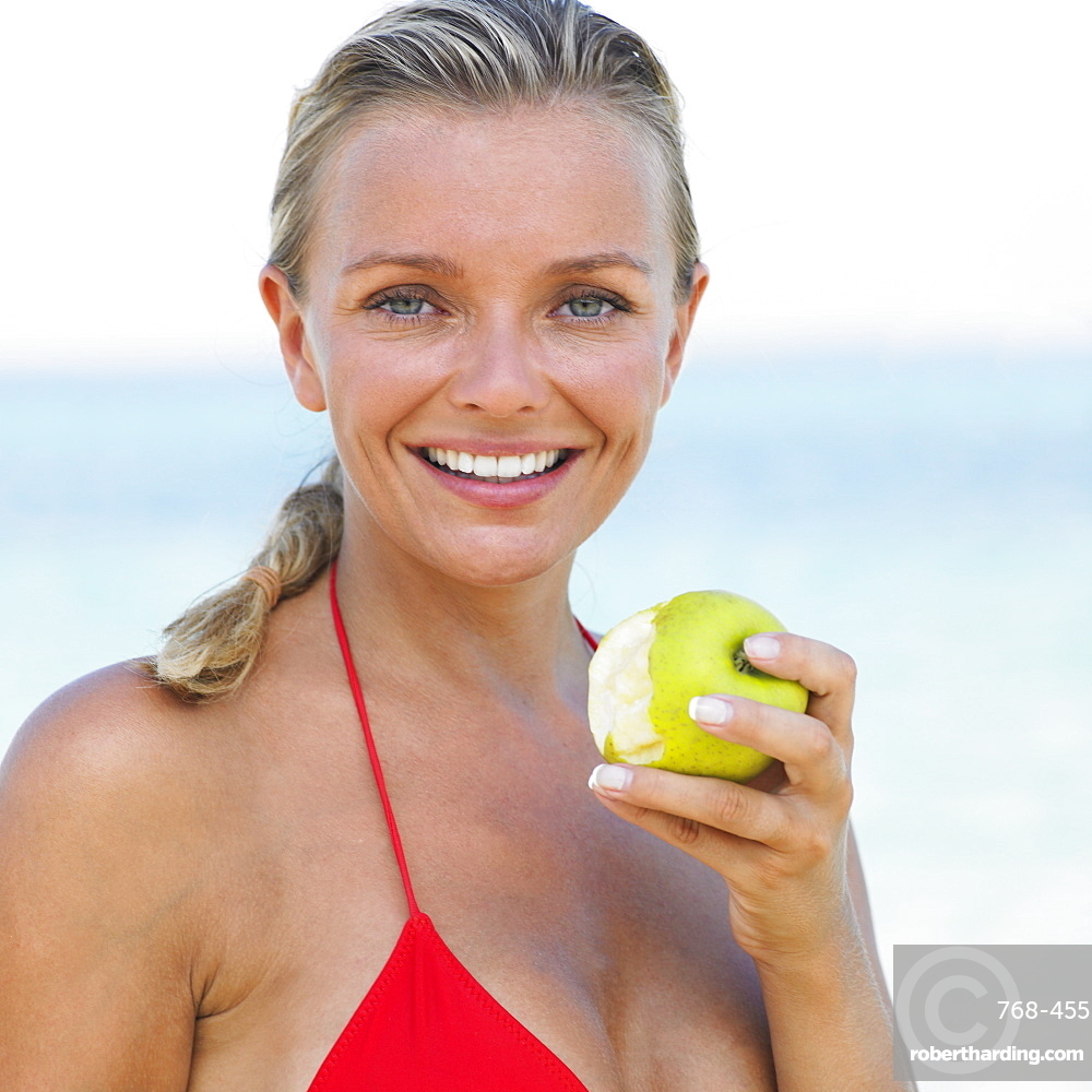 Woman in bikini on beach holding apple