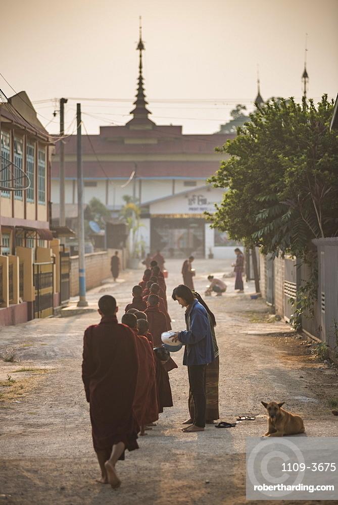 Young novice monks collecting alms at sunset in Pindaya, Shan State, Myanmar (Burma)