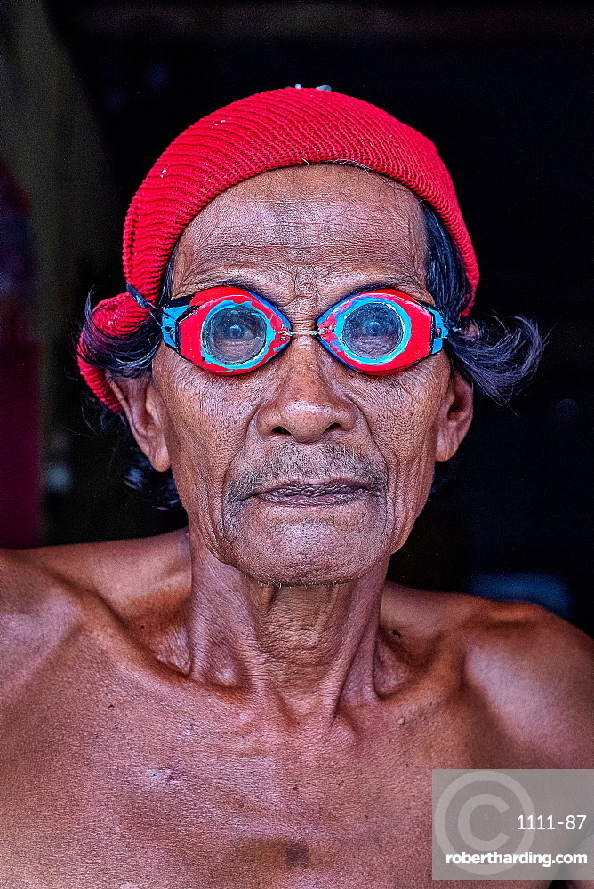 Portrait of a Bajau fisherman wearing crafted wooden goggles from mangrove wood, Togian Island, Indonesia, Southeast Asia, Asia