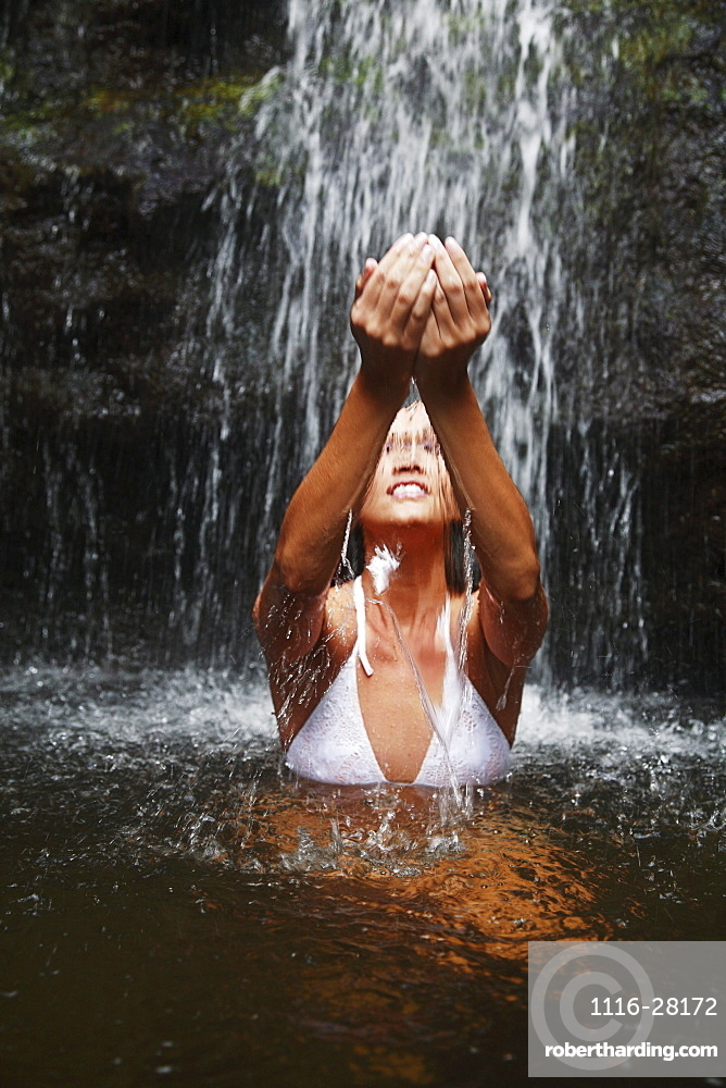 Hawaii, Oahu, Manoa Falls, Beautiful female sitting at the bottom of Manoa Waterfall, cupping water above her.