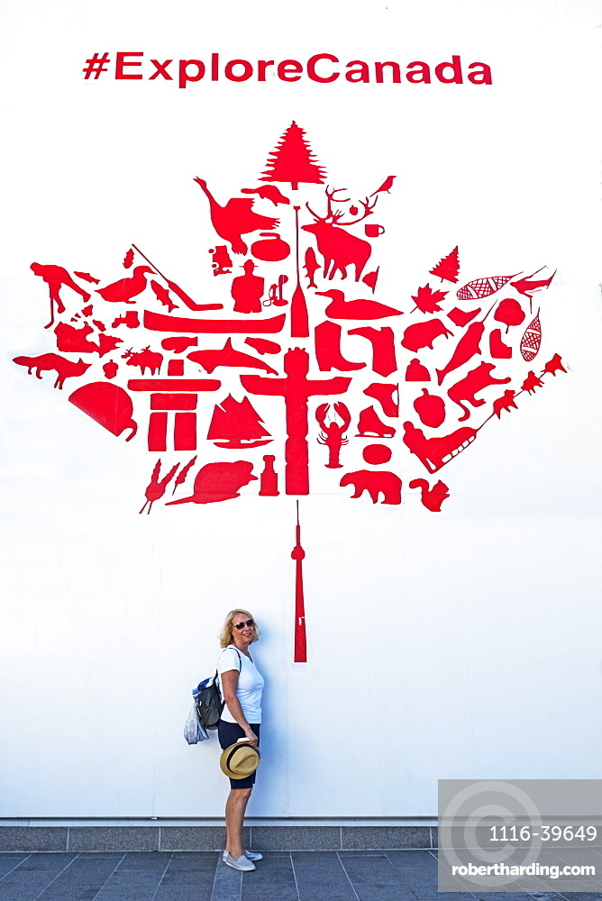 A female tourist stands under a red and white maple leaf wall mural promoting Canadian tourism, Vancouver, British Columbia, Canada