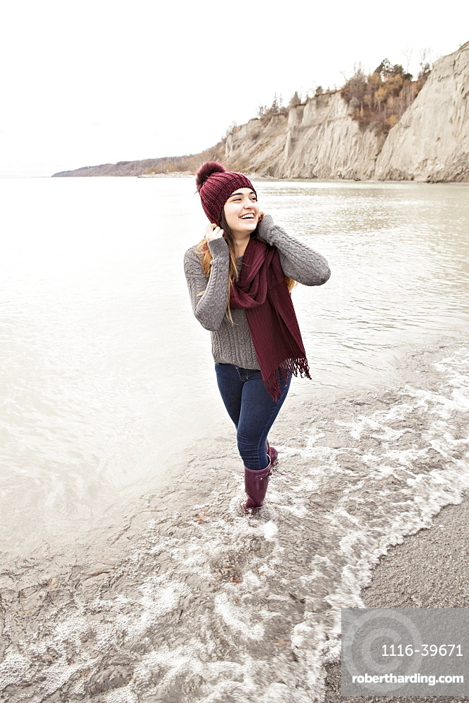 Girl standing in shallow water in autumn at the Scarborough Bluffs wearing a knit hat and scarf, Toronto, Ontario, Canada