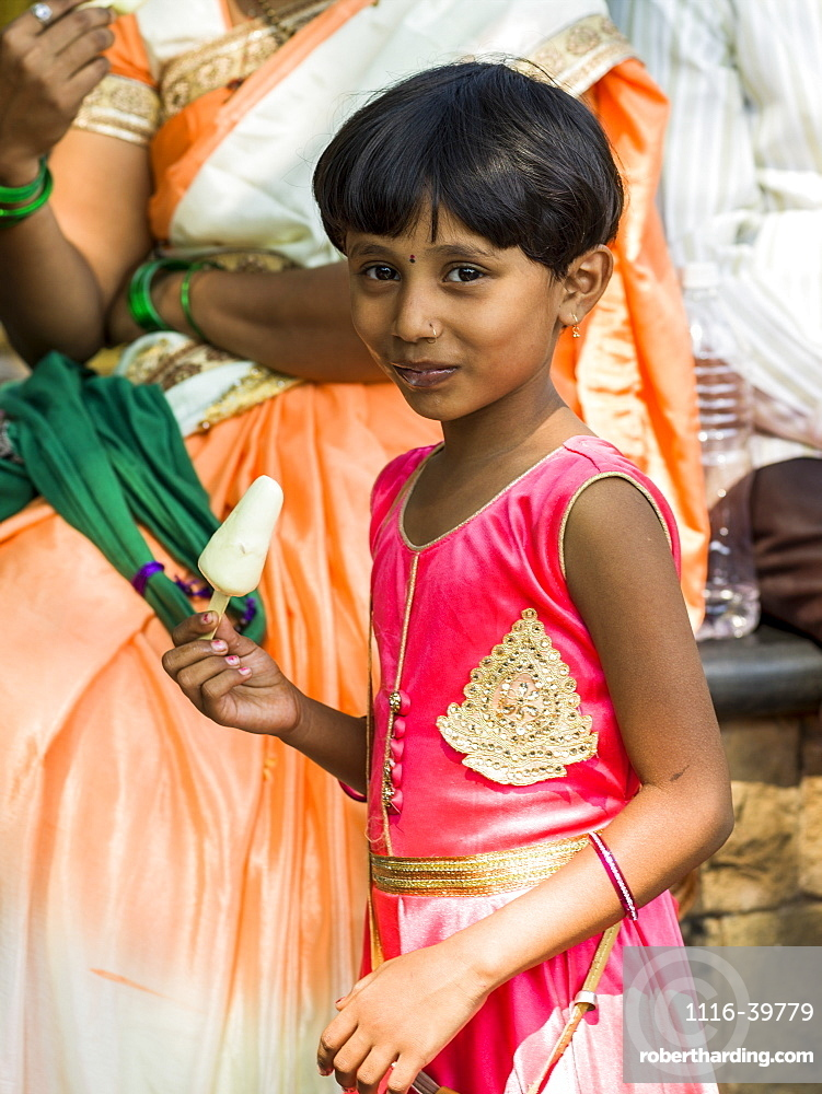 A young girl in a bright pink dress eating a popsicle and smiling for the camera, Mumbai, Maharashtra, India