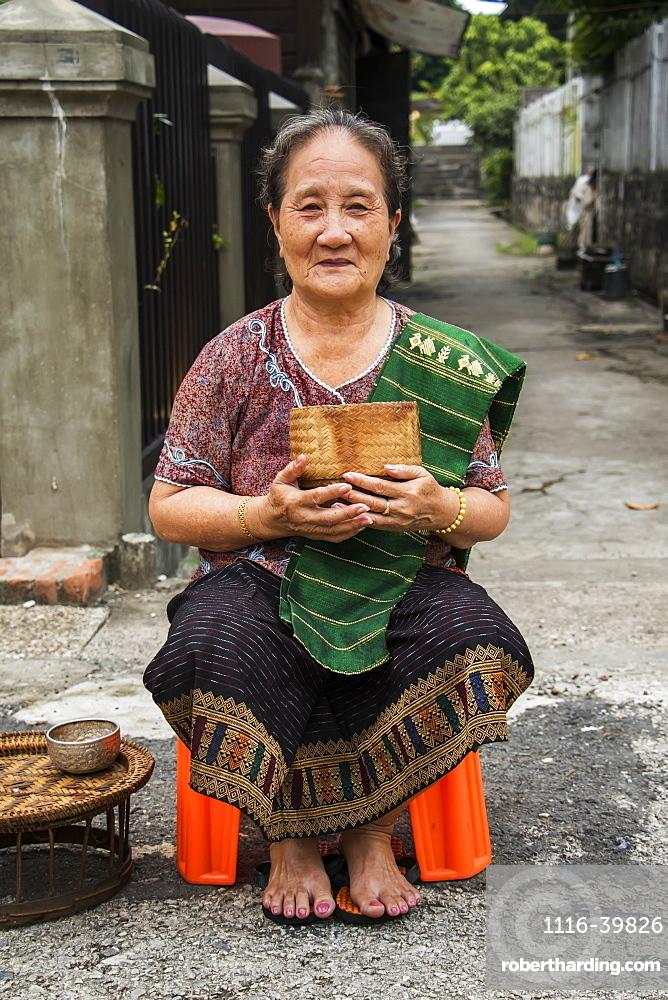 Woman waiting to give Buddhist monks alms on Khounsua Road at dawn, Luang Prabang, Luang Prabang, Laos