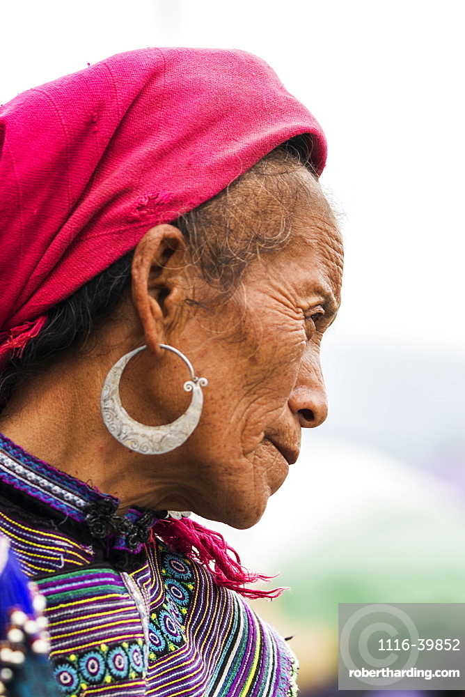 Portrait of a senior woman wearing a headscarf and earrings with colourful dress, Bac Ha, Lao Cai, Vietnam