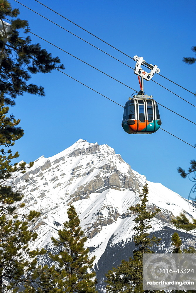 Gondola pod travelling along cables with snow covered mountain and blue sky in the background framed by evergreen trees, Banff National Park, Banff, Alberta, Canada