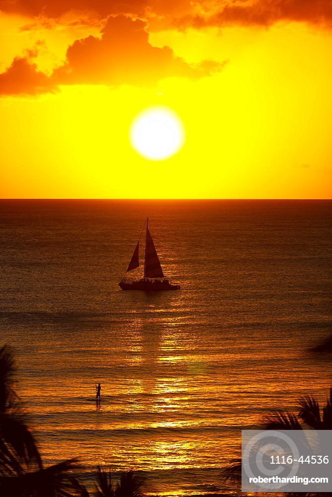 Golden sunset off Waikiki Beach with a silhouetted sailboat in the water, Honolulu, Oahu, Hawaii, United States of America