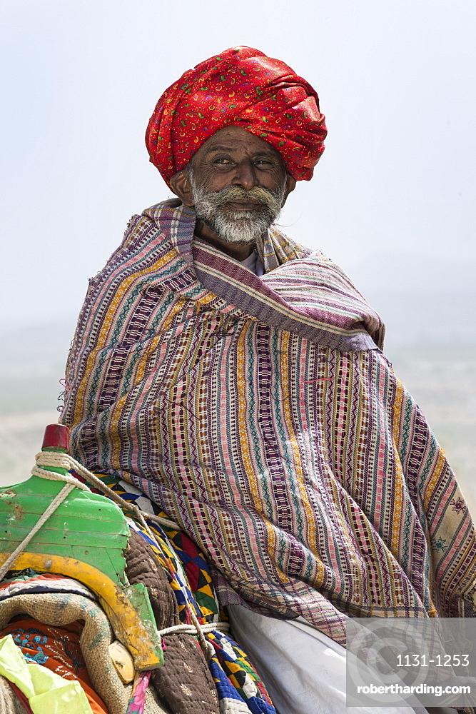 Man of the Dhebariya Rabari community in traditional cloth with a dromedary, Great Rann of Kutch Desert, Gujarat, India, Asia